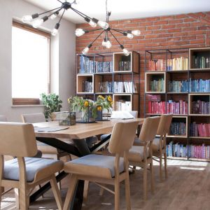 W jadalni ustawiony został bardzo duży, masywny stół na osiem osób z nogami o konstrukcji metalowej oraz ciekawa biblioteczka. Projekt: Ewelina Mikulska-Ignaczak, Mikulska Studio. Fot. Jakub Ignaczak, K1M1