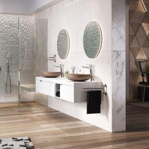 W tej aranżacji strefa prysznica powstała przy ścianie pokrytej ciekawą, srebrzystą mozaiką. Nie ma brodzika, zastosowano odpływ liniowy. Posadzka tworzy w łazience jednolitą całość. Do kompozycji wybrano zestaw podtynkowy z baterią i deszczownią Algeo Set. Fot. ferro