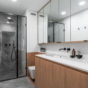W tej łazience strefę prysznica zaprojektowano we wnęce z drzwiami prysznicowymi w modnej matowej czerni. Zestawy prysznicowy jest podtynkowy i idealnie pasuje do całości. Projekt: Anna Maria Sokołowska, Katarzyna Nowak, pracownia Anna Maria Sokołowska Architektura Wnętrz. Zdjęcia: Fotomohito