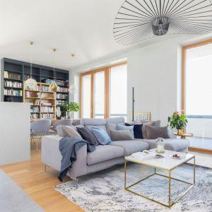 Szary narożnik idealnie pasuje do jasnej kolorystki oraz drewna zastosowanego w salonie. Projekt: Renee's Interior Design. Fot. Marta Behling Pion Poziom - Fotografia Wnętrz