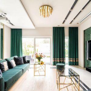 Jasny salon ożywia piękna, butelkowa zieleń oraz elementy w kolorze złotym. Projekt: Trędowska Design. Fot Michał Bachulski