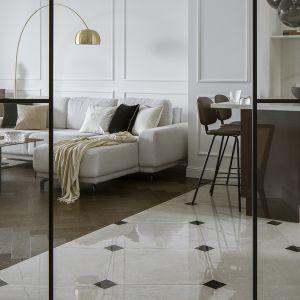 Sztukateria na ścianie i podłoga ułożona w jodełkę stanowią kanwę aranżacji salonu. Projekt Kate&Co. Mieszkanie Koneser. Fot.Yassen Hristov