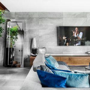 Ścianę za telewizorem wyłożono wielkoformatowymi płytkami. Projekt Agnieszka Morawiec. Fot. Dekorialove