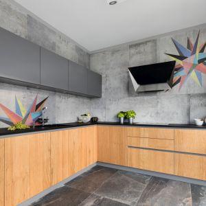 Szare płytki doskonale imitują beton dodając kuchni surowego charakteru. Projekt Magdalena Lehmann.