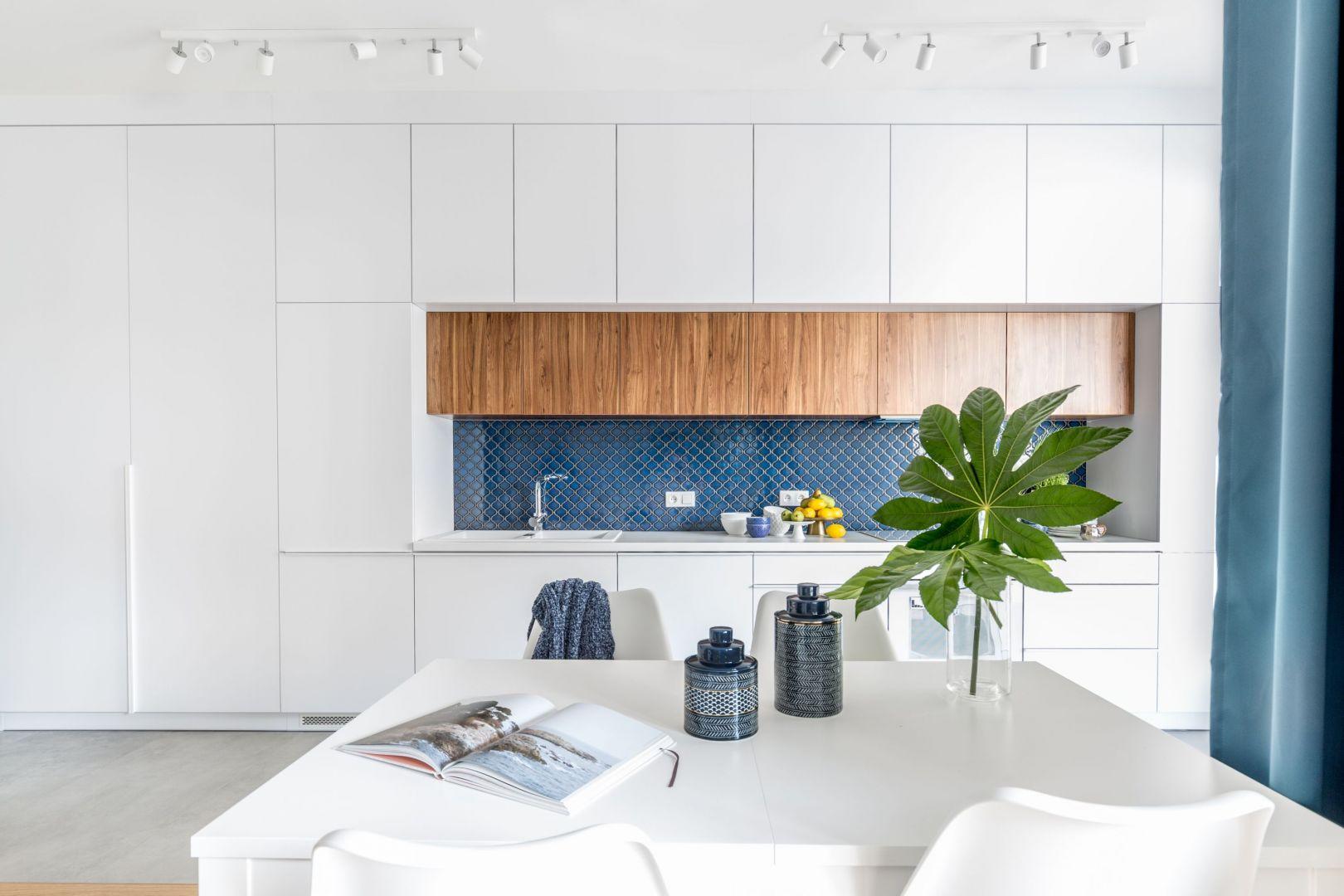 W kuchni w bloku, zwłaszcza w aneksie kuchennym warto postawić na jasne lub białe meble kuchenne, które powiększą optycznie pomieszczenie. Kolorowe płytki nad blatem ożywią aranżację. Projekt: Monika Pniewska. Fot. Pion Poziom
