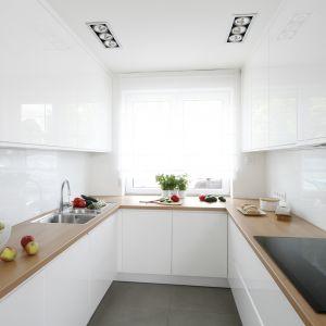 Na ścianie nad blatem w kuchni w bloku znalazło się białe szkło. Projekt: Joanna Ochota. Fot. Bartosz Jarosz