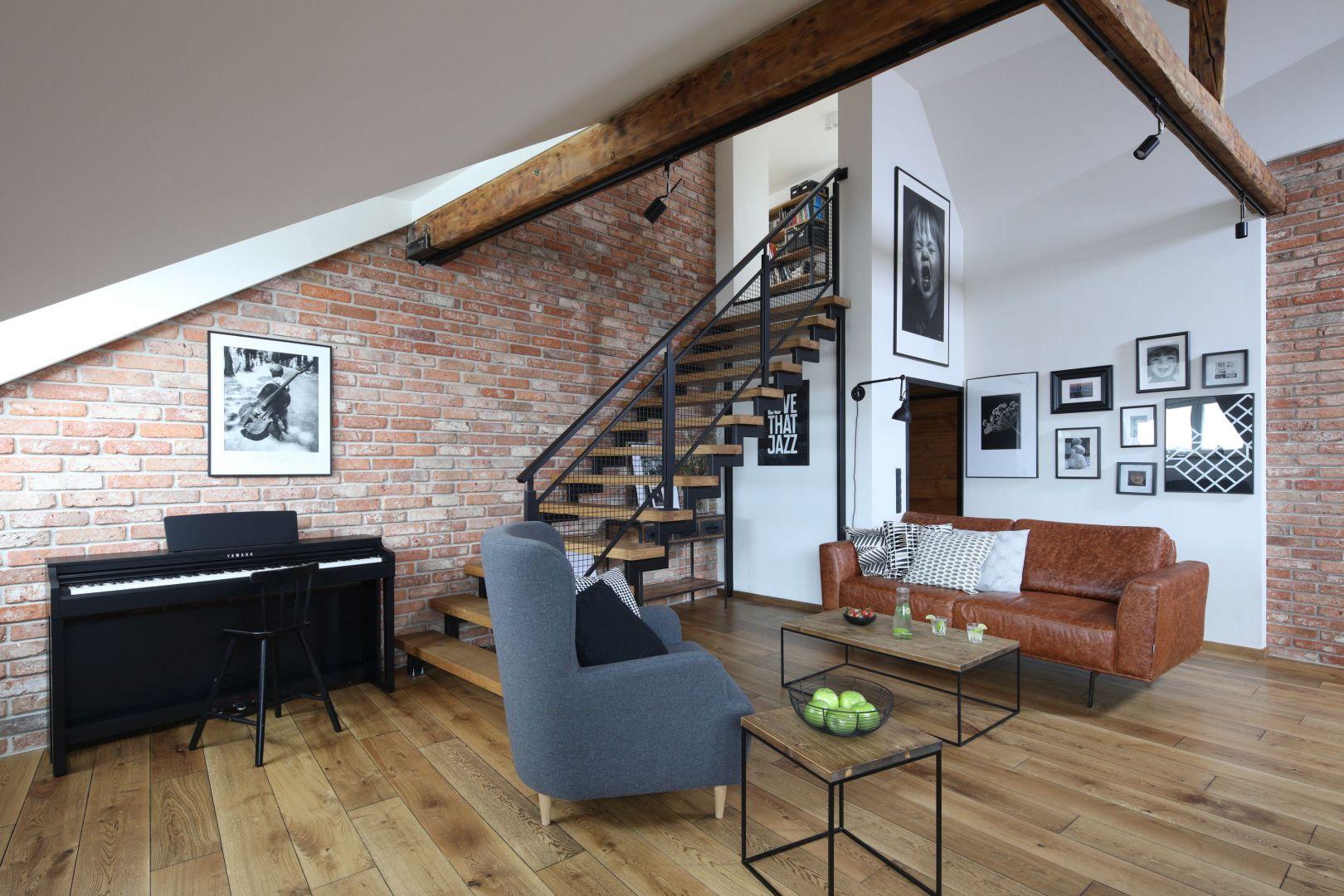 Cegła w salonie pięknie pasuje do białych ścian, drewnianej podłogi i metalowych schodów. Projekt: Katarzyna Walawska. Fot. Bartosz Jarosz