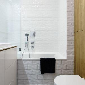 Ściany w łazience wykończono białym płytkami o małym formacie oraz drewnem. Projekt: Magdalena Bielicka, Maria Zrzelska-Pawlak, pracownia Magma. Fot. Fotomohito