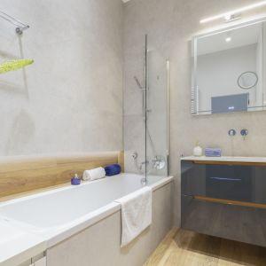 Ściany w łazience wykończone są szarymi płytkami oraz płytami imitującymi drewno. Projekt: Renee's Interior Design. Fot. Marta Behling, Pion Poziom - Fotografia Wnętrz