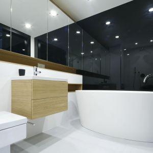 Ściany w łazience wykończono czarnym szkłem oraz białymi płytkami ceramicznymi. Projekt: Monika i Adam Bronikowscy. Fot. Bartosz Jarosz