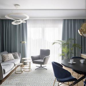 Niebieskie zasłony w stylu hotelowym wnoszą powiew elegancji do tego salonu. Projekt:  MIKOŁAJSKA studio. Fot. Jakub Dziedzic