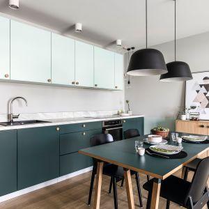 Kuchnia w stylu vinate, całkowicie otwarta na salon, dolne szafki ciemnozielone, górne - jasne. Projekt: Raca Architekci. Fot. Fotomohito