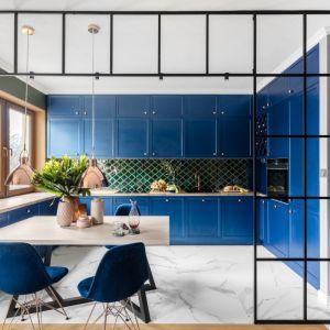 Ciemnoniebieska duża kuchnia, oddzielona od salonu szklaną loftową ścianką z metalowymi szprosami. Projekt: Marta Wierzbicka-Patejuk Pracownia Pięknych Wnętrz. Fot. Aleksandra Dermont Ayuko Studio