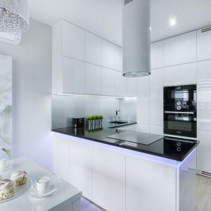 Ściana nad blatem w kuchni wykończona została szkłem w białym kolorze. Projekt: Justyna Mojżyk, poliFORMA. Fot. Monika Filipiuk-Obałek