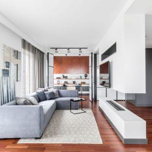 Biały salon ociepla drewniana podłoga oraz dywan i zasłony. Projekt: Decoroom. Fot. Pion Poziom