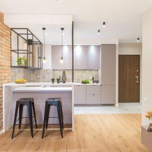 Szary kolor zabudowy kuchennej dobrze komponuje się z cegłą. Projekt Decoroom. Fot. Pion Poziom