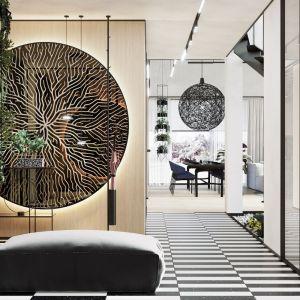 Rośliny zwisają się ze specjalnie zaprojektowanych kwietników w strefie wejściowej, w części salonu i kuchni. Projekt wnętrza: Paweł Łęczycki, modeko.studio