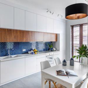 Proste białe szafki kuchenne w macie i ożywiająca je kolorowa mozaika. Projekt Monika: Pniewska. Fot. Marta Behling/Pion Poziom