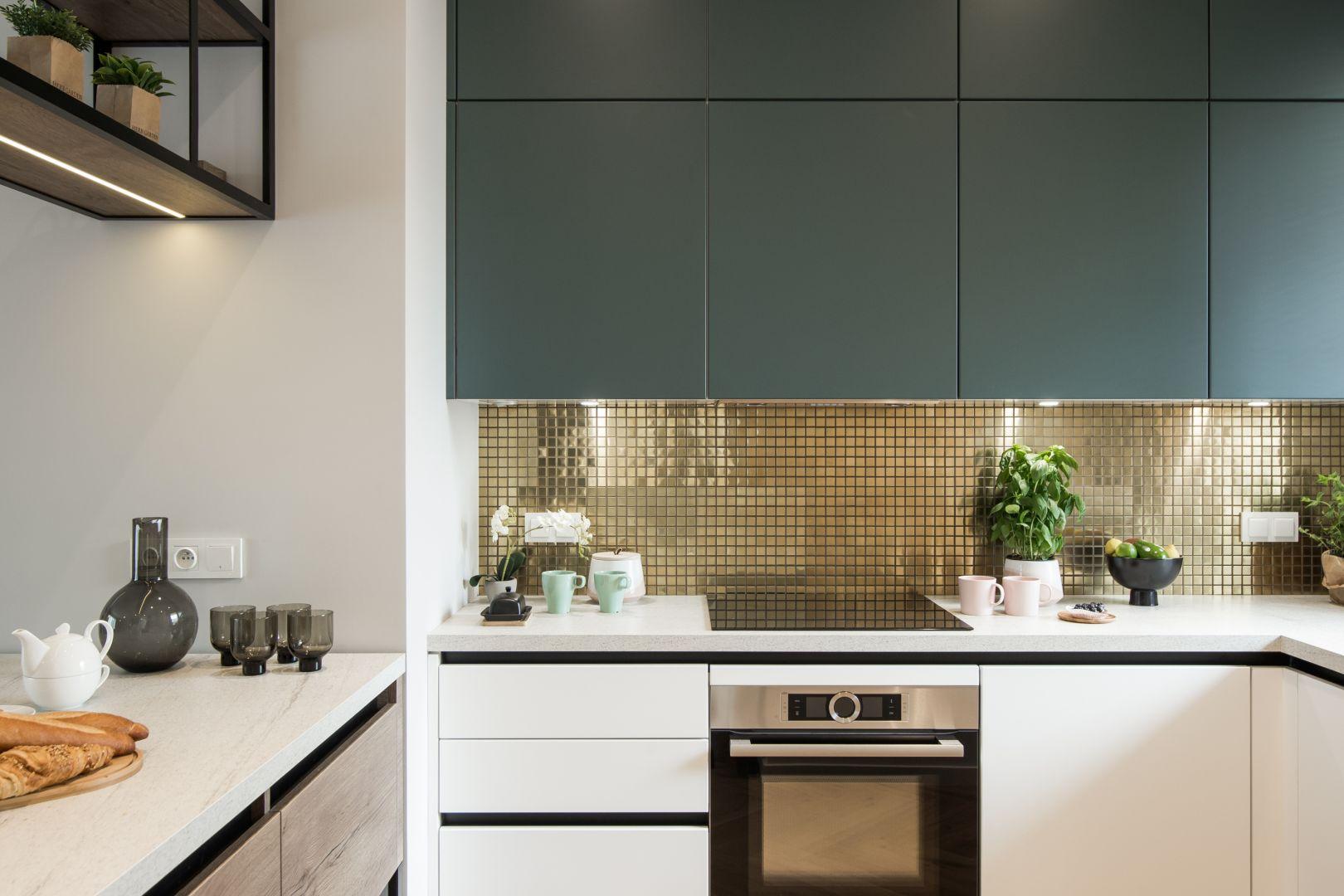 Zielone fronty kuchenne i złota mozaika. Projekt: Kodo Projektowanie Wnętrz