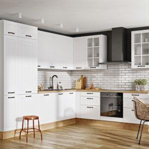 Klasyka w nowoczesnym wydaniu, która łączy tradycyjne wzornictwo z eleganckim minimalizmem. Białe fronty mebli z ozdobnymi frezami i przeszkleniami współgrają z białą cegłą pomiędzy zabudową meblową. Idealnie się komponują, tworząc harmonijną całość nawiązującą do skandynawskiej prostoty, ocieplonej elementami drewna.  Fot. KAM