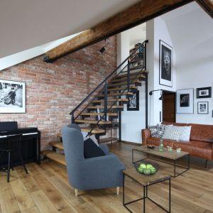 Szary fotel świetnie pasuje do brązowej sofy w salonie oraz do cały na ścianie. Projekt: Katarzyna Walawska. Fot. Bartosz Jarosz