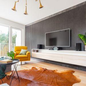 Żółty fotel pięknie ożywia nowoczesny salon w szarościach.   Projekt: Joanna Rej, Gama design. Fot. Pion Poziom