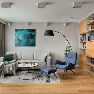 Niebieski fotel z podnóżkiem w jasnym salonie. Realizacja: Ilona Paleńczuk z zespołem IP Design. Fot. Mikołaj Dąbrowski