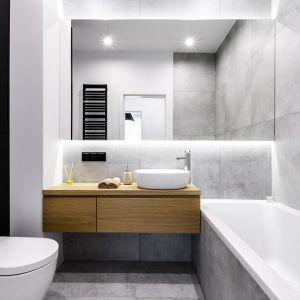 Gres łazienkowy w kamiennym stylu można także przełamać czarnymi frontami zabudowy, w której da się sprytnie ukryć stelaż toalety. Projekt i zdjęcia: Moovin Interiors