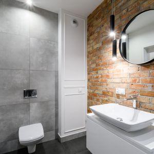 Z racji tego, że cegła uwielbia towarzystwo betonu, dobrym rozwiązaniem będzie również położenie na jednej ze ścian płytek ceramicznych w cementowym odcieniu. Projekt i zdjęcia: Moovin Interiors