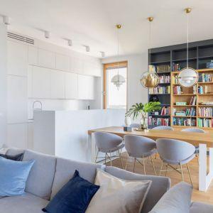Regał na książki w salonie otwartym na jadalnię i kuchnię zajmuje aż całą ścianę. Projekt: Renee's Interior Design Fot. Marta Behling Pion Poziom - Fotografia Wnętrz