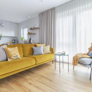 Sofa w kolorze żółtym w modnym, szarym salonie wygląda super. Projekt: Decoroom. Fot. Marta Behling, Pion Poziom