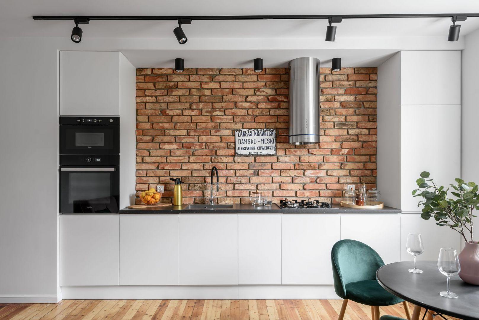 Częścią salonu jest też jednorzędowy aneks kuchenny w białym kolorze. Projekt: Magdalena i Robert Scheitza, pracownia SHLTR Architekci