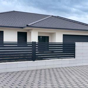 Kolor szary to jedna z typowych barw wykorzystywanych w architekturze ogrodowej i na elewacjach budynków. Fot. Plast-Met Systemy Ogrodzeniowe