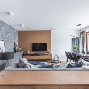 Ścianę za telewizorem zdobi panel z rysunkiem drewna. Projekt Decoroom. Fot. Pion Poziom