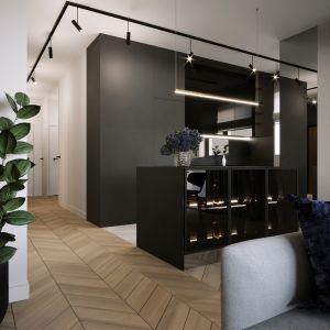Architekci zaproponowali niezwykle modne w ostatnich latach rozwiązanie - kuchnię otwartą na salon, jednak z wyraźnym podziałem tych dwóch przestrzeni. Projekt i zdjęcia: Moovin Interiors