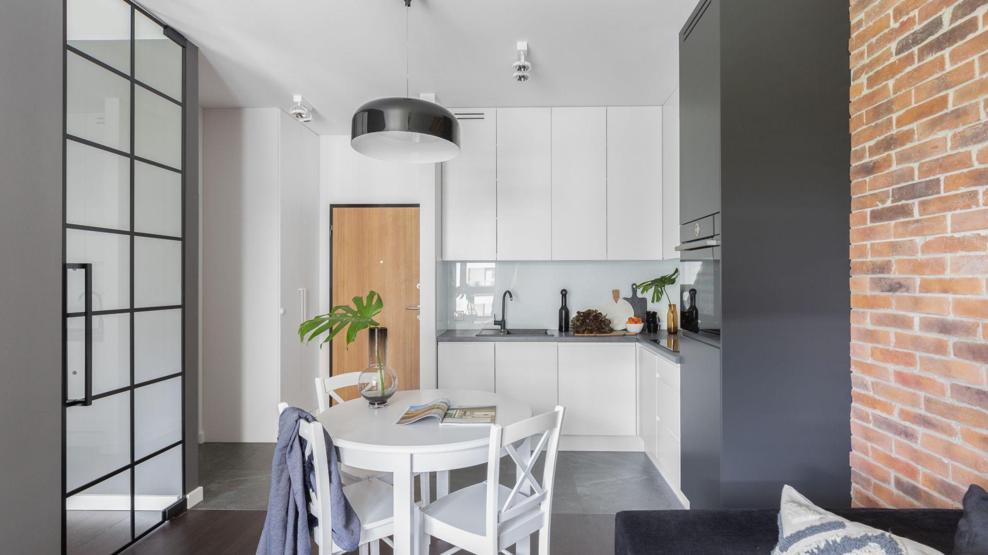 Mała kuchnia w białym kolorze połączona z salonem. Projekt: Emilia Rusińska, Decoroom
