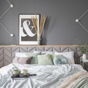 W sypialni pierwsze skrzypce gra drewniane łóżko z szerokim, tapicerowanym we wzór jodełki zagłówkiem. Projekt: Zu Projektuje. Fot. Pion Poziom