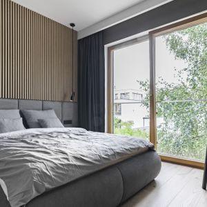 Ścianę za łóżkiem zdobi drewno i tapicerowany zagłówek. Projekt: KAEL Architekci. Foto Rafał Chojnacki