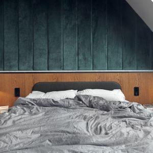 Ściana za łóżkiem została wykończona płytą fornirowaną, w którą został wkomponowany tapicerowany zagłówek. Ściana nad drewnianą lamperią to tapicerowane panele z zielonego weluru. Projekt: Marta i Michał Raca, Raca Architekci. Fot. Tom Kurek