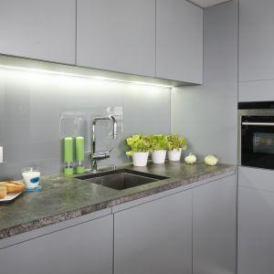 Ścianę nad blatem w kuchni zdobi szare szkło. Projekt Monika i Adam Bronikowscy. Fot. Bartosz Jarosz
