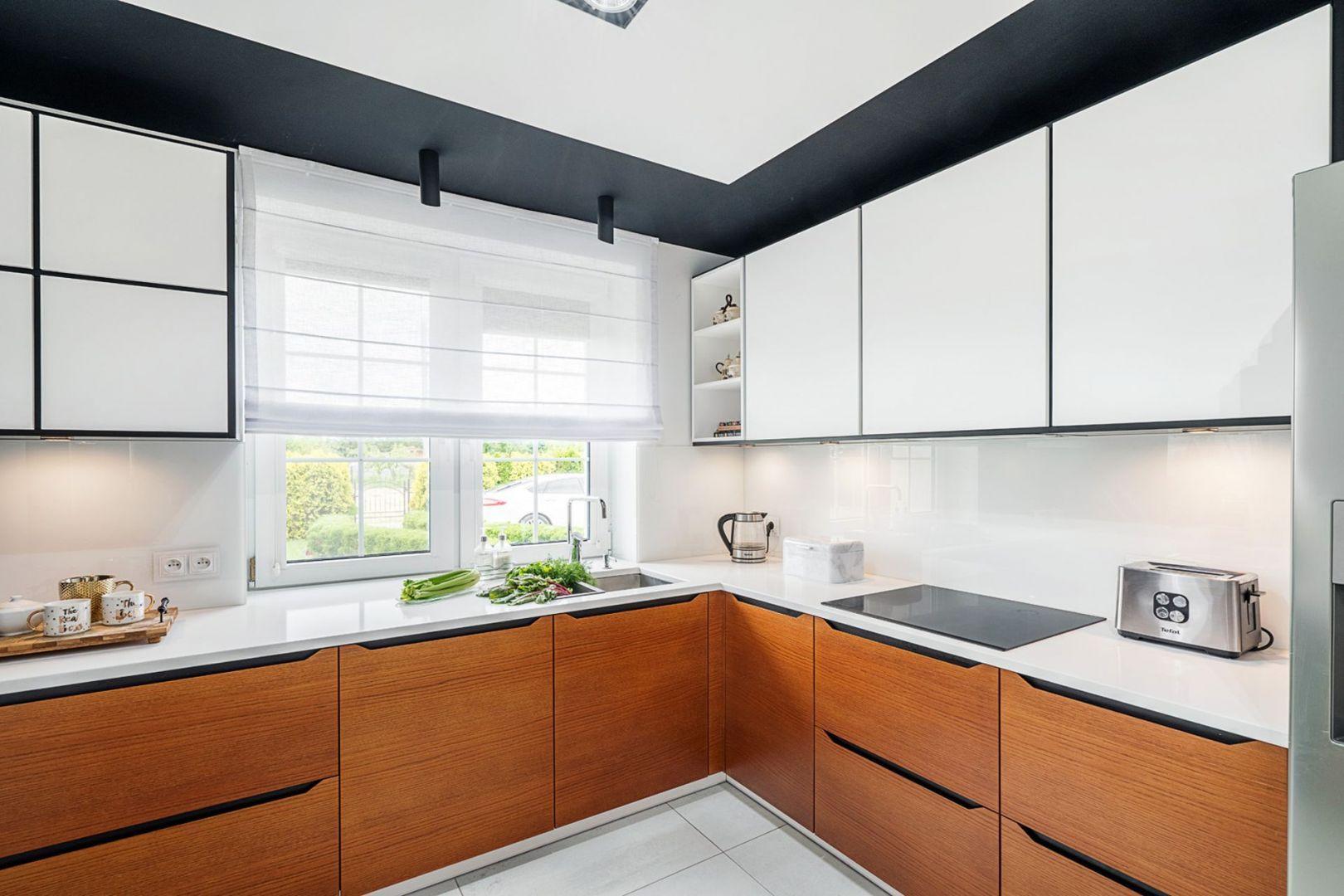 Ściana nad blatem w kuchni wykończona została szkłem w białym kolorze. Projekt: Magdalena Kaczmarka, mDesignStudio. Współpraca: Dekorian Home. Fot. Artur Krupa