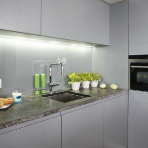 Ściana nad blatem w kuchni wykończona została szkłem w szarym kolorze. Projekt: Monika i Adam Bronikowscy. Fot. Bartosz Jarosz