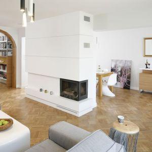 Narożny kominek w salonie ma piękną obudowę w białym kolorze. Projekt: Agata Piltz. Fot. Bartosz Jarosz