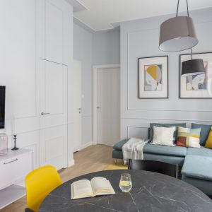 Dominującą w aranżacji salonu neutralną szarość ożywiają żółte tony w postaci dywanu, poduszek i grafik na ścianie. Projekt: Decoroom. Fot. Pion Poziom