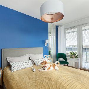 Ściana w kolorze kobaltu stała się tłem dla prostego, tapicerowanego łóżka. Projekt: Justyna Mojżyk, poliFORMA. Fot. Monika Filipiuk-Obałek