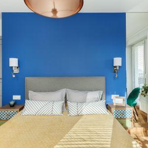 Duża tafla lustra nie tylko powiększa i rozświetla przestrzeń, ale także koryguje proporcje ukrywając, że łóżko zostało ustawione asymetrycznie względem całej ściany. Projekt: Justyna Mojżyk, poliFORMA. Fot. Monika Filipiuk-Obałek