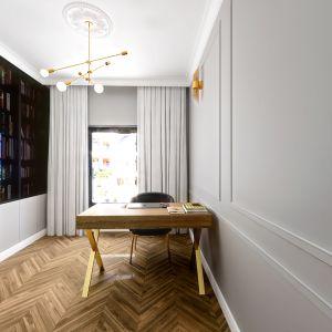 Wygodny gabinet z biurkiem i ogromną biblioteką zaprojektowaną na jednej ścianie. Projekt i wizualizacje: Monika Staniec