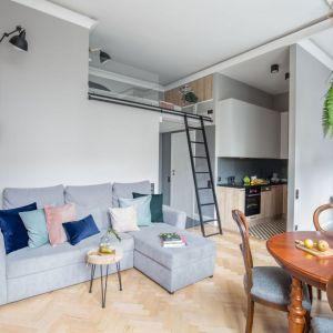 Salon połączony z kuchnią, jadalnią i sypialnią w kawalerce. Projekt: Monika Pniewska. Fot. Marta Behling / Pion Poziom