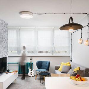 Mały salon, w którym ściana za telewizorem stawni najmocniejszy punkt całej aranżacji. Projekt i zdjęcia: Kasia Kokot (Pracownia Inside)