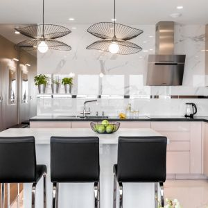 Kuchnię od salonu oddziela wygodna wyspa w białym kolorze, która pełni również rolę jadalni. Projekt i zdjęcia: Monika Staniec